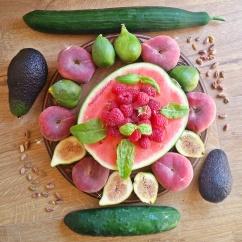 Art de fruits - pastèque, figues fraîches, pêches des vignes, concombres avocats, framboises et feuilles de basilic et d'oseille